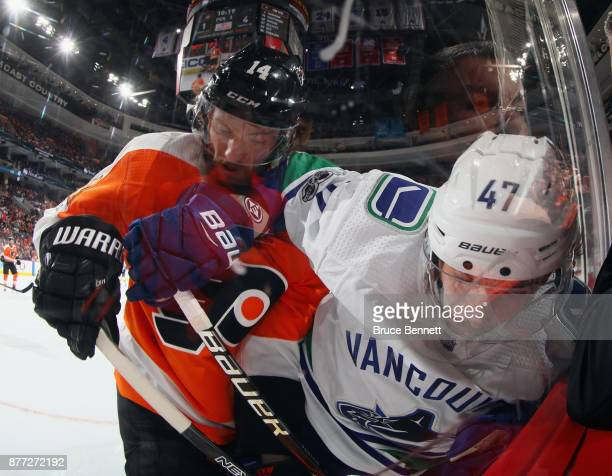 Sean Couturier of the Philadelphia Flyers checks Sven Baertschi of the Vancouver Canucks into the glass during the third period at the Wells Fargo...
