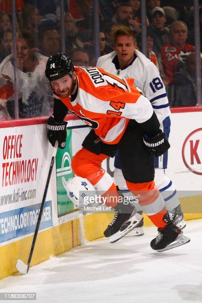 Sean Couturier of the Philadelphia Flyers checks the helmet off of Andreas Johnsson of the Toronto Maple Leafs in the second period at the Wells...