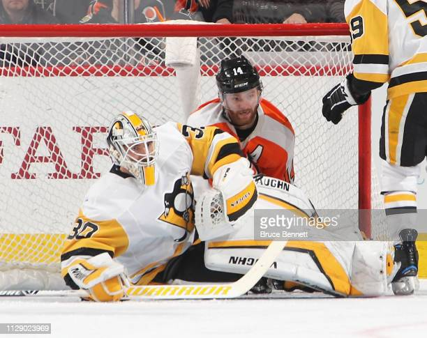 Sean Couturier of the Philadelphia Flyers falls into the back of the net behind Matt Murray of the Pittsburgh Penguins during the first period at the...