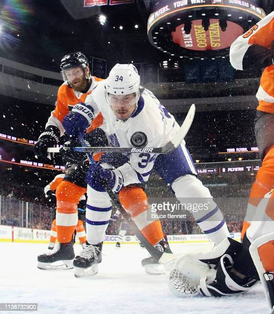 Sean Couturier of the Philadelphia Flyers fights for control of the puck with Auston Matthews of the Toronto Maple Leafs during the first period at...