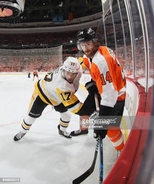Sean Couturier of the Philadelphia Flyers is checked by Bryan Rust of the Pittsburgh Penguins during the second period in Game Three of the Eastern...