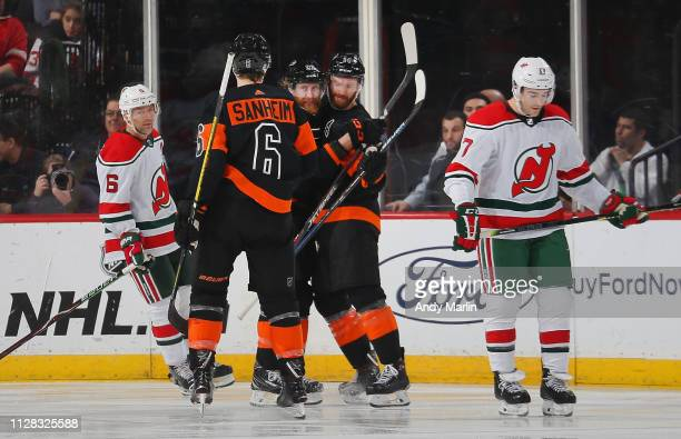 Sean Couturier of the Philadelphia Flyers is congratulated by his teammates as Andy Greene and Kenny Agostino of the New Jersey Devils look away...
