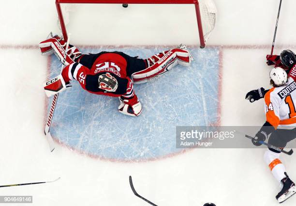 Sean Couturier of the Philadelphia Flyers scores a goal past Cory Schneider of the New Jersey Devils during the first period at the Prudential Center...
