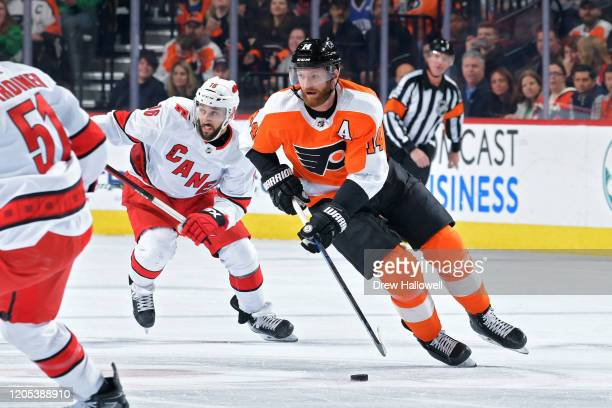 Sean Couturier of the Philadelphia Flyers skates ahead of Vincent Trocheck of the Carolina Hurricanes in the first period at Wells Fargo Center on...