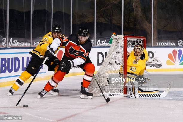 Sean Couturier of the Philadelphia Flyers skates with the puck pressured by Patrice Bergeron of the Boston Bruins during the 'NHL Outdoors At Lake...