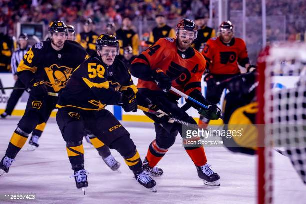 Sean Couturier sees his shot go in the net as pressuring Penguin Jake Guentzel watches on during the Stadium Series game between the Pittsburgh...