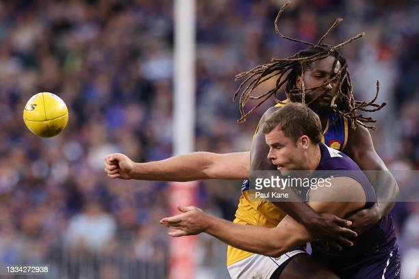 Sean Darcy of the Dockers gets his handball away under pressure by Nic Naitanui of the Eagles during the round 22 AFL match between the Fremantle...