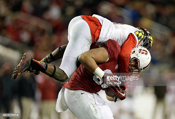 Sean Davis of the Maryland Terrapins jumps on Austin Hooper of the Stanford Cardinal to tackle him during the Foster Farms Bowl at Levi's Stadium on...