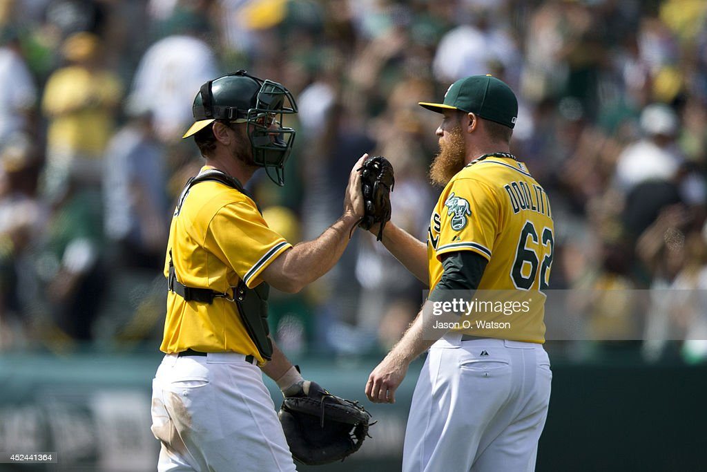 Sean Doolittle #62 of the Oakland Athletics celebrates with John Jaso #5 after the game against the Baltimore Orioles at O.co Coliseum on July 20, 2014 in Oakland, California. The Oakland Athletics defeated the Baltimore Orioles 10-2.