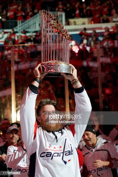 Sean Doolittle of the Washington Nationals holds the Commissioner's Trophy as the Nationals are honored during a pregame ceremony to celebrate the...