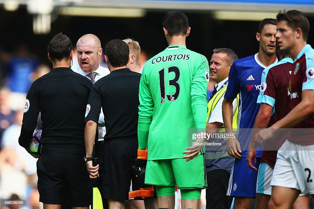 Sean Dyche, Manager of Burnley (White Shirt) has words with referee Mark Clattenburg (L) during the Premier League match between Chelsea and Burnley at Stamford Bridge on August 27, 2016 in London, England.