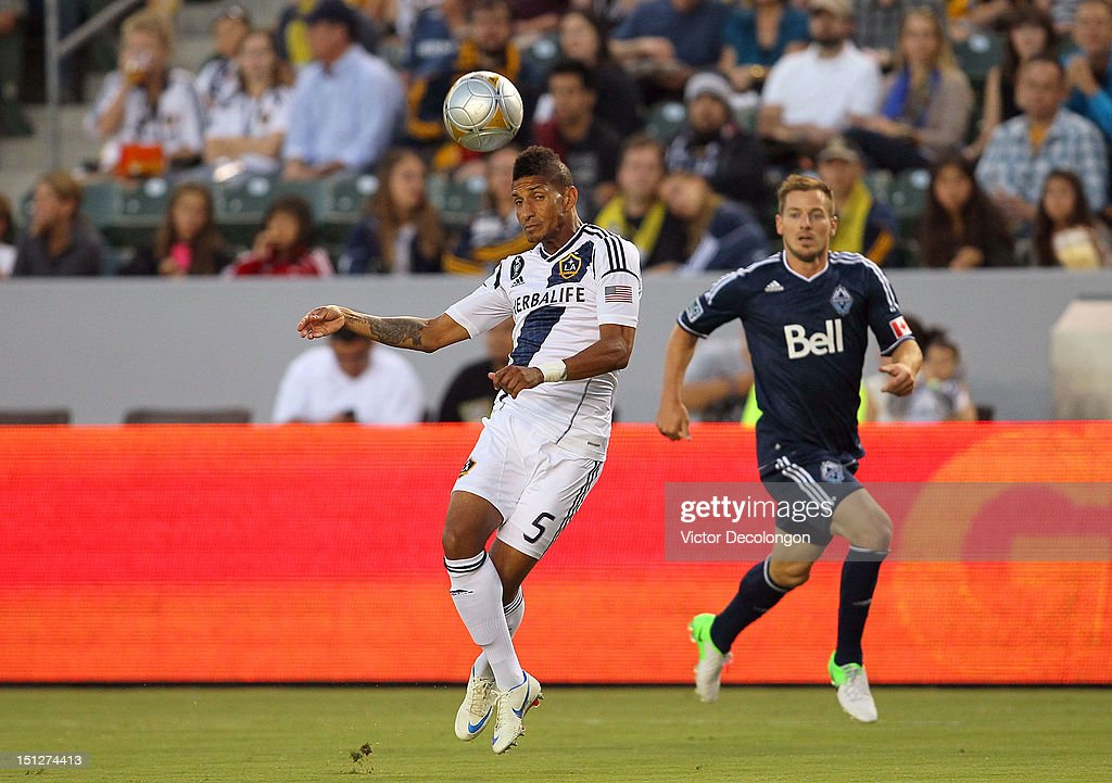 Sean Franklin #5 of the Los Angeles Galaxy heads the ball clear from Jordan Harvey #3 of the Vancouver Whitecaps during the MLS match at The Home Depot Center on September 1, 2012 in Carson, California. The Galaxy defeated the Whitecaps 2-0.