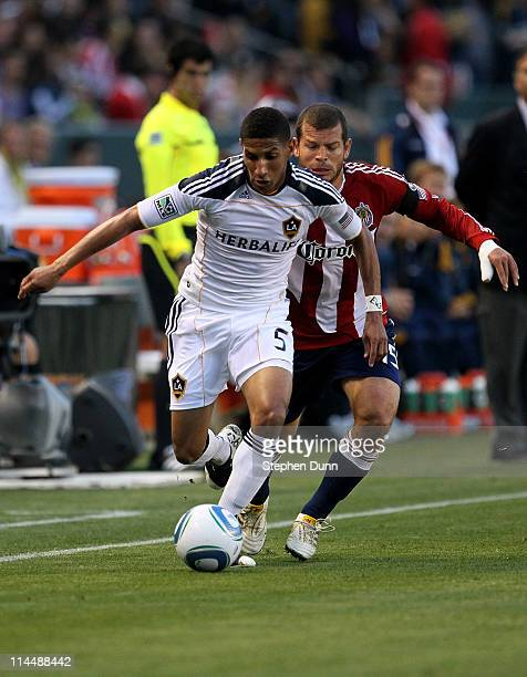 Sean Franklin of the Los Angeles Galaxy runs with the ball ahead of Alejandro Moreno of Chivas USA at The Home Depot Center on May 21 2011 in Carson...