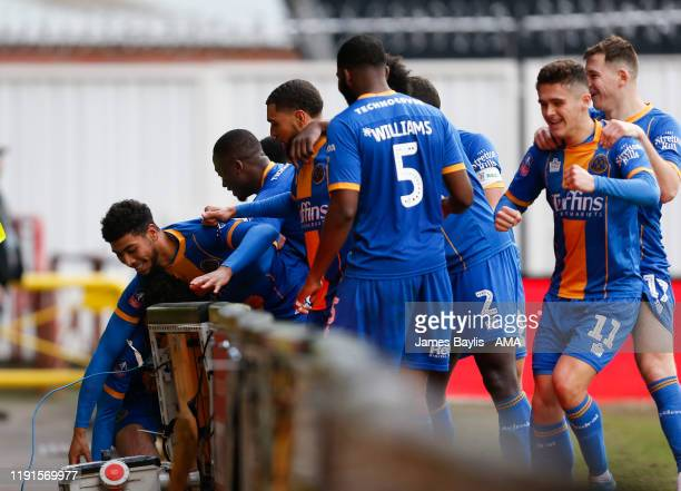 Sean Goss of Shrewsbury Town falls through the advertising boards as he celebrates with his team mates after scoring a goal to make it 1-1 during the...