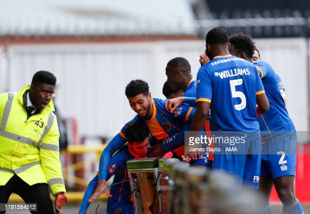 Sean Goss of Shrewsbury Town falls through the advertising boards as he celebrates with his team mates after scoring a goal to make it 11 during the...