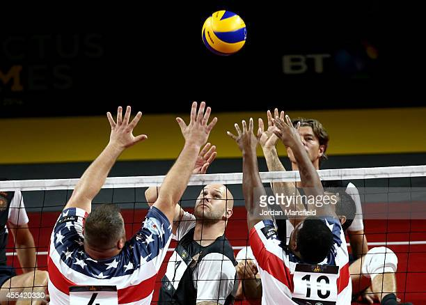 Sean Hook and Monica Southall of the USA block a shot by Frens Hartgers of the Netherlands during the Sitting Volleyball match between the USA and...