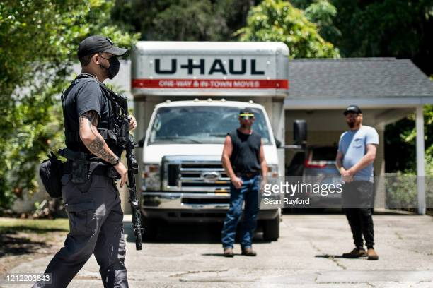 Sean Joesph, a former Marine Sgt., provides armed protection for protesters as Satilla Shores residents look on May 8, 2020 in Brunswick, Georgia....