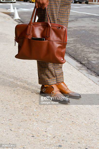Sean Julian seen at Skylight Clarkson Sq outside the Orley show wearing Suit Supply pants Ben Minkoff brown leather bag and Canali shoes during New...