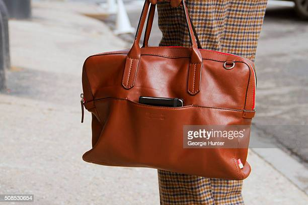 Sean Julian seen at Skylight Clarkson Sq outside the Orley show wearing Suit Supply pants and Ben Minkoff brown leather bag during New York Fashion...