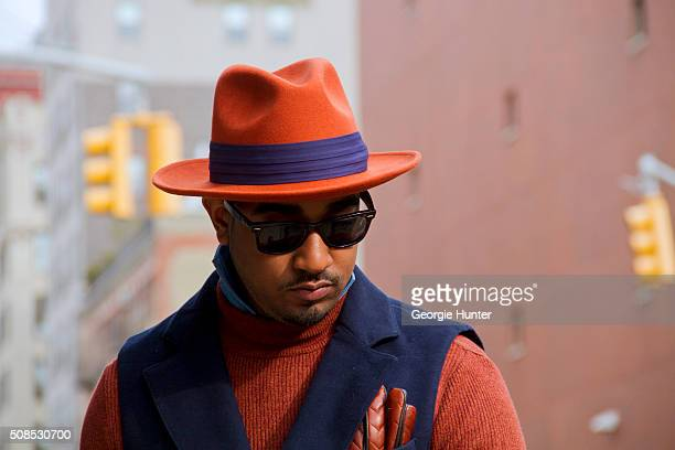 Sean Julian seen at Skylight Clarkson Sq outside the Orley show wearing Suit Supply jacket and shirt vintage orange hat with purple ribbon and RayBan...