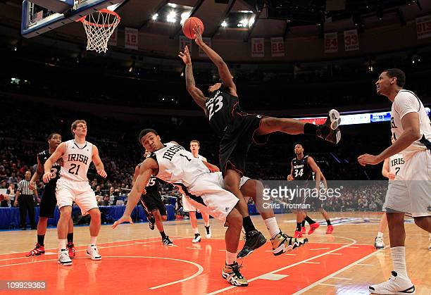 Sean Kilpatrick of the Cincinnati Bearcats drives with the ball against Tyrone Nash of the Notre Dame Fighting Irish during the quarterfinals of the...