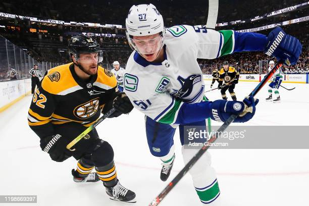 Sean Kuraly of the Boston Bruins and Tyler Myers of the Vancouver Canucks battle for the puck during a game at TD Garden on February 4, 2020 in...