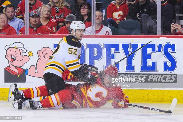 Sean Kuraly of the Boston Bruins checks Rasmus Andersson of the Calgary Flames during an NHL game at Scotiabank Saddledome on October 17 2018 in...