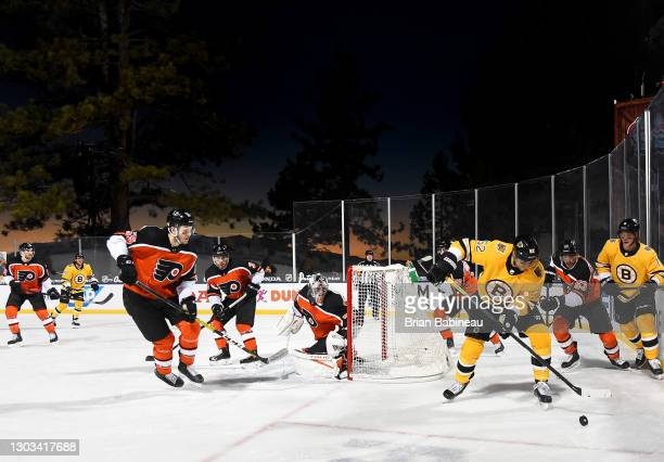 Sean Kuraly of the Boston Bruins controls the puck in the corner while Samuel Morin of the Philadelphia Flyers looks on during the second period of...