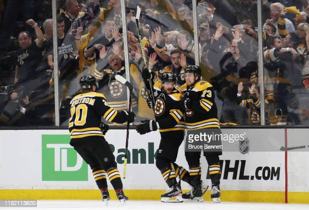 Sean Kuraly of the Boston Bruins is congratulated by his teammates Joakim Nordstrom and Charlie McAvoy after scoring a third period goal against the...