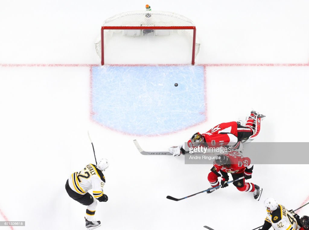 Sean Kuraly #52 of the Boston Bruins scores the game-winning overtime goal against Craig Anderson #41 and Erik Karlsson #65 of the Ottawa Senators in Game Five of the Eastern Conference First Round during the 2017 NHL Stanley Cup Playoffs at Canadian Tire Centre on April 21, 2017 in Ottawa, Ontario, Canada.