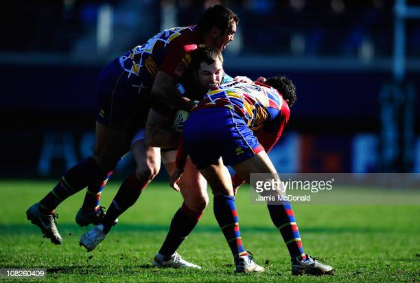 Sean Lamont of Scarlets is tackled by Mermoz Maxime and Mas Nicolas during the Heineken Cup Pool 5 match between Perpignan and Scarlets at the Stade...