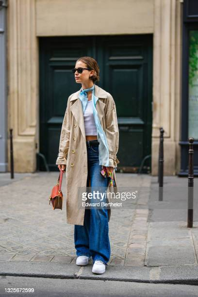 Sean Levyy wears a white ribbed crop-top / t-shirt, a pale blue shirt, a pale blue scarf, a beige long coat, blue denim ripped jeans pants, a...