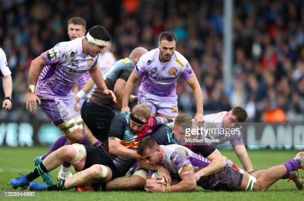 Sean Lonsdale of Exeter Chiefs is tackled by James Chisholm and Alex Dombrandt of Harlequins during the semi-final of the Premiership Rugby Cup...