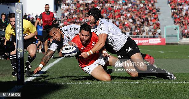 Sean Maitland of Saracens dives over for the first try despite being tackled by Ma'a Nonu and Leigh Halfpenny during the European Rugby Champions Cup...