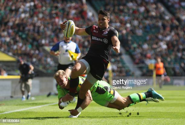 Sean Maitland of Saracens evades Harry Mallinder of Northampton Saints to score their fifth try during the Aviva Premiership match between Saracens...