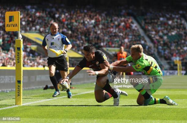 Sean Maitland of Saracens scores their third try as Harry Mallinder of Northampton Saints attempts to tackle during the Aviva Premiership match...