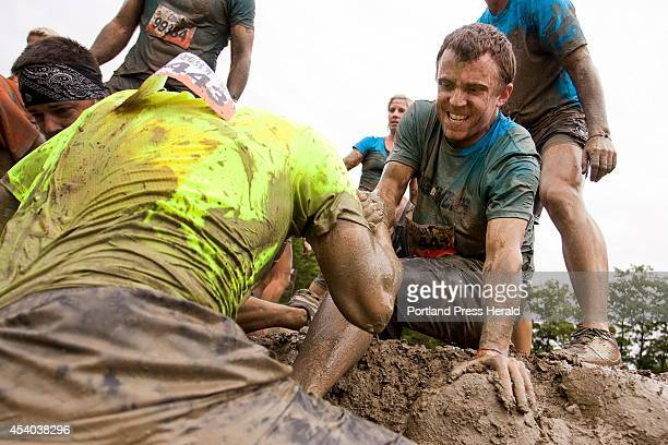 Sean McLean of Scarborough top pulls a fellow competitor up the finish of the 'Mud Mile' while competing in the Tough Mudder obstacle course in...