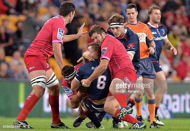 Sean McMahon of the Rebels is wrapped up by the Reds defence during the round 14 Super Rugby match between the Queensland Reds and the Melbourne...