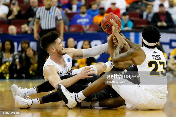 Sean Mobley and Issac Vann of the Virginia Commonwealth Rams battles for the ball with Aubrey Dawkins of the UCF Knights in the second half during...
