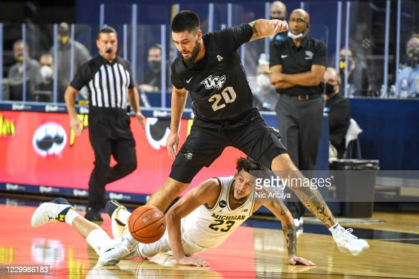 Sean Mobley of the UCF Knights jumps over Brandon Johns Jr. #23 of the Michigan Wolverines after they both went for a loose ball during the first...