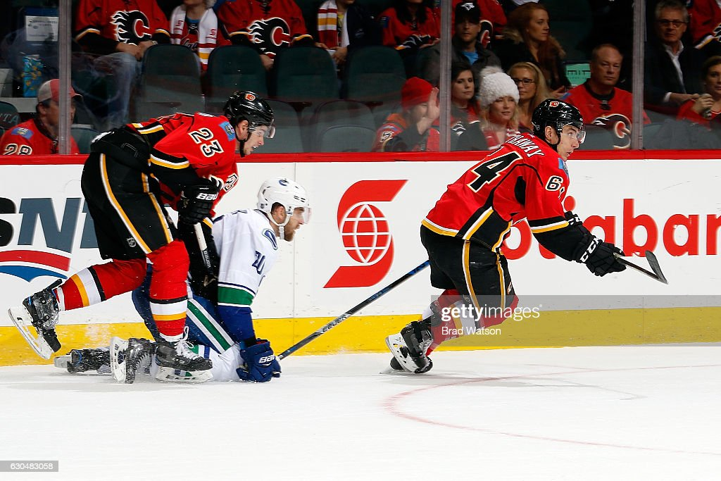 Sean Monahan #23 and Garnet Hathaway #64 of the Calgary Flames skate against Brandon Sutter #20 of the Vancouver Canucks during an NHL game on December 23, 2016 at the Scotiabank Saddledome in Calgary, Alberta, Canada.