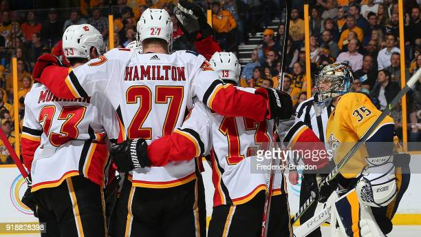 Sean Monahan Michael Stone and Johnny Gaudreau of the Calgary Flames celebrate a goal against goalie Pekka Rinne of the Nashville Predators during...