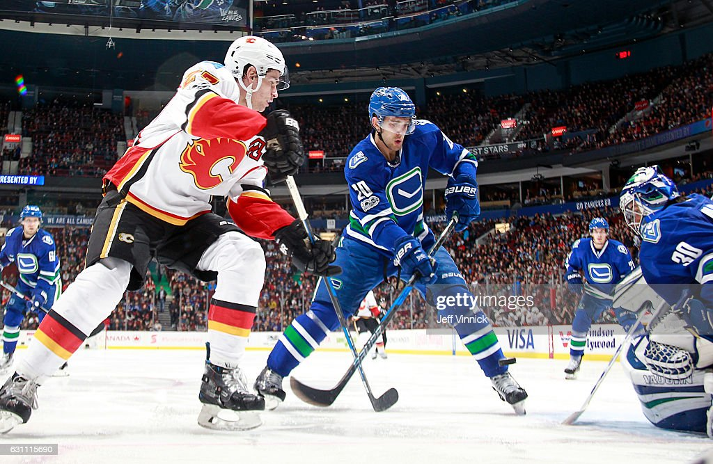 Sean Monahan #23 of the Calgary Flames and Brandon Sutter #20 of the Vancouver Canucks look for a rebound as Ryan Miller #30 of the Vancouver Canucks makes a save during their NHL game at Rogers Arena January 6, 2017 in Vancouver, British Columbia, Canada. Vancouver won 4-2.