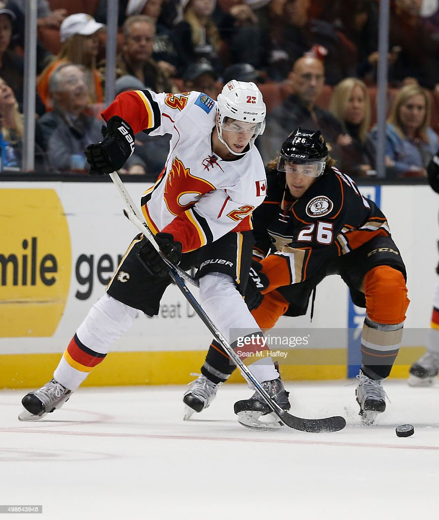 Sean Monahan #23 of the Calgary Flames battles for a loose puck with Carl Hagelin #26 of the Anaheim Ducks during the third period of a game at Honda Center on November 24, 2015 in Anaheim, California.