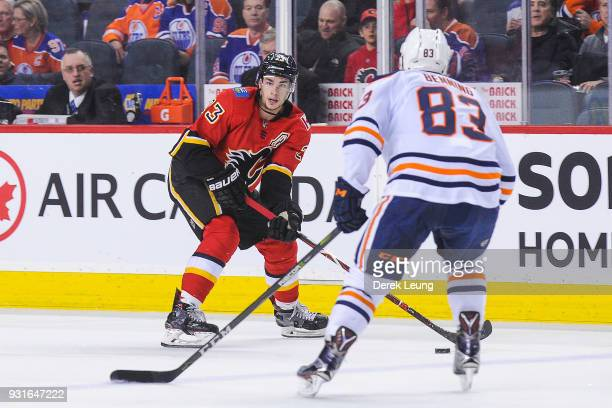 Sean Monahan of the Calgary Flames carries the puck against Matthew Benning of the Edmonton Oilers during an NHL game at Scotiabank Saddledome on...
