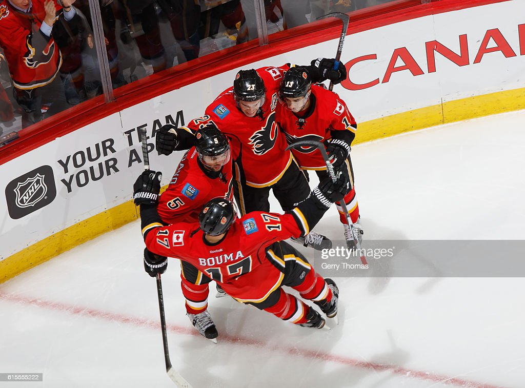 Sean Monahan #23 of the Calgary Flames celebrates with teammates after a goal against the Buffalo Sabres at Scotiabank Saddledome on October 18, 2016 in Calgary, Alberta, Canada.