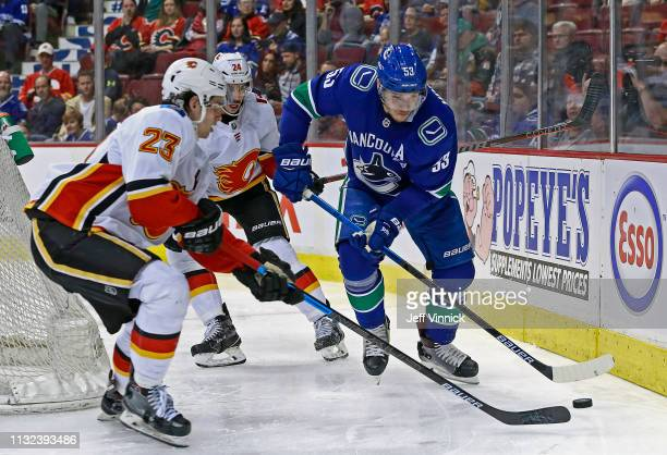 Sean Monahan of the Calgary Flames checks Bo Horvat of the Vancouver Canucks during their NHL game at Rogers Arena March 23 2019 in Vancouver British...