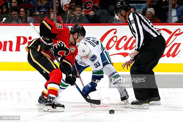 Sean Monahan of the Calgary Flames faces off against Bo Horvat of the Vancouver Canucks during an NHL game on December 23 2016 at the Scotiabank...