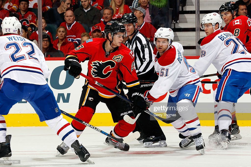 Sean Monahan #23 of the Calgary Flames faces off against David Desharnais #51 of the Montreal Canadiens during an NHL game at Scotiabank Saddledome on October 30, 2015 in Calgary, Alberta, Canada.