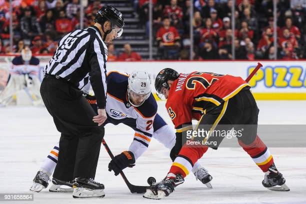 Sean Monahan of the Calgary Flames facesoff against Leon Draisaitl of the Edmonton Oilers during an NHL game at Scotiabank Saddledome on March 13...
